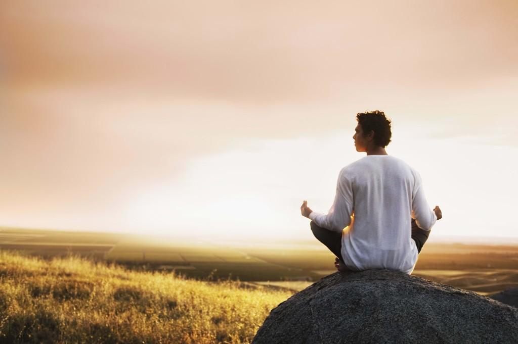 man-meditation-stone-field-morning